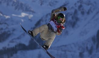 United States' Jamie Anderson takes a jump during the women's snowboard slopestyle qualifying at the Rosa Khutor Extreme Park ahead of the 2014 Winter Olympics, Thursday, Feb. 6, 2014, in Krasnaya Polyana, Russia. (AP Photo/Sergei Grits)