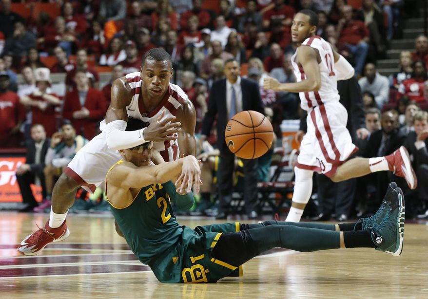 Baylor center Isaiah Austin, bottom, passes the ball in front of Oklahoma guard Buddy Hield in the second half of an NCAA college basketball game in Norman, Okla., Saturday, Feb. 8, 2014. Oklahoma won 88-72. Oklahoma guard Jordan Woodard(10) looks on. (AP Photo/Sue Ogrocki)