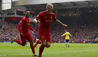 Liverpool's Martin Skrtel, centre, celebrates after scoring his first goal against Arsenal during their English Premier League soccer match at Anfield Stadium, Liverpool, England, Saturday Feb. 8, 2014. (AP Photo/Jon Super)