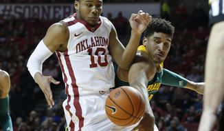 Baylor guard Ish Wainright, right, knocks the ball away from Oklahoma guard Jordan Woodard (10) in the first half of an NCAA college basketball game in Norman, Okla., Saturday, Feb. 8, 2014. (AP Photo/Sue Ogrocki)