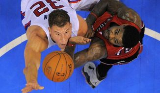 Los Angeles Clippers forward Blake Griffin, left, puts up a shot as Toronto Raptors forward Amir Johnson defends during the first half of an NBA basketball game, Friday, Feb. 7, 2014, in Los Angeles. (AP Photo/Mark J. Terrill)