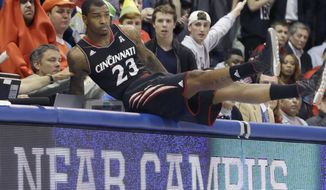 Cincinnati guard Sean Kilpatrick lands on the scorer's tables after chasing a loose ball during the first half of an NCAA college basketball game against SMU on Saturday, Feb. 8, 2014, in Dallas. (AP Photo/LM Otero)  vcb