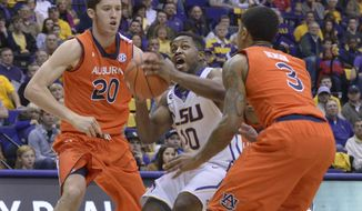 LSU's Andre Stringer looks for a shot as Auburn's Alex Thompson, left, and Chris Denson defend during an NCAA college basketball game Saturday, Feb. 8, 2014, in Baton Rouge, La. (AP Photo/The Advocate,Heather McClelland) MAGS OUT, INTERNET OUT, TV OUT, NO SALES, NO FORNS. LOUISIANA BUSINESS INC. OUT (INCLUDING GREATER BATON ROUGE BUSINESS REPORT, 225, 10/12, INREGISTER, LBI CUSTOM