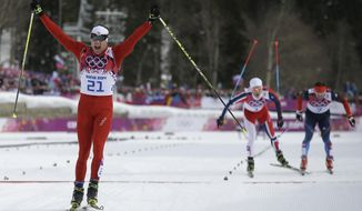 Switzerland's Dario Cologna celebrates winning the gold medal as Norway's Martin Johnsrud Sundby, second from right, and Russia's Maxim Vylegzhanin are to cross the finish line during the men's cross-country 30k skiathlon at the 2014 Winter Olympics, Sunday, Feb. 9, 2014, in Krasnaya Polyana, Russia. (AP Photo/Gregorio Borgia)