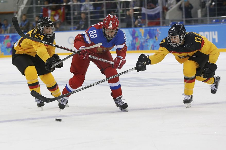 Yekaterina Smolina of Russia is sandwiched between Lisa Christine Schuster, left and Sara Seiler of Germany as they battle for the puck during the first period of the 2014 Winter Olympics women's ice hockey game at Shayba Arena, Sunday, Feb. 9, 2014, in Sochi, Russia. (AP Photo/Petr David Josek)