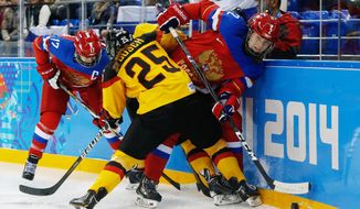 Yekaterina Smolentseva of Russia (17), Franziska Busch of Germany (25) and Angelina Khomich of Russia (2) battle against the board during the second period of the 2014 Winter Olympics women's ice hockey game at Shayba Arena, Sunday, Feb. 9, 2014, in Sochi, Russia. (AP Photo/Petr David Josek)
