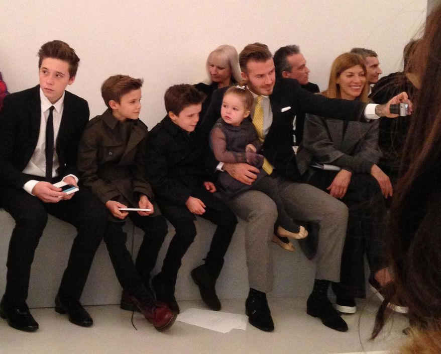 David Beckham takes a photo of his four children in the front row before the Victoria Beckham show, as daughter Harper sits in Beckham's lap Sunday Feb. 9, 2014, during Fashion Week in New York.  (AP Photo/Jocelyn Noveck)