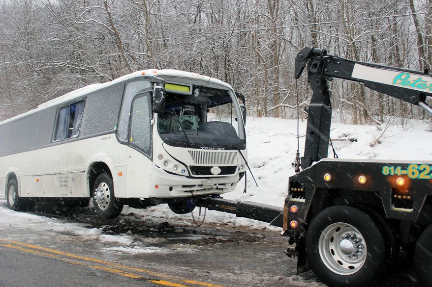 A bus is towed after the driver lost control and struck an embankment on Route 220 in Cumberland Valley Twp., Pa., Sunday, Feb. 9, 2014, according to the police. More than 20 passengers were injured in the crash. (AP Photo/Bedford Gazette, Bridgett Weaver)