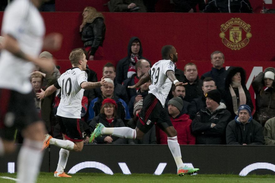 Fulham's Darren Bent, centre, celebrates after scoring an injury time goal against Manchester United during their English Premier League soccer match at Old Trafford Stadium, Manchester, England, Sunday Feb. 9, 2014. (AP Photo/Jon Super)