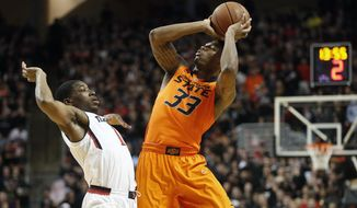 Oklahoma State's Marcus Smart (33) shoots over Texas Tech's Randy Onwuasor (1) during their NCAA college basketball game in Lubbock, Texas, Saturday, Feb, 8, 2014. (AP Photo/Lubbock Avalanche-Journal, Tori Eichberger)