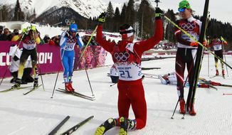 Switzerland's Dario Cologna, center, celebrates winning the the men's cross-country 30k skiathlon as, from left, Germany's Tobias Angerer, Italy's Giorgio  di Centa and Norway's Petter Northug look at the 2014 Winter Olympics, Sunday, Feb. 9, 2014, in Krasnaya Polyana, Russia. (AP Photo/Gregorio Borgia)