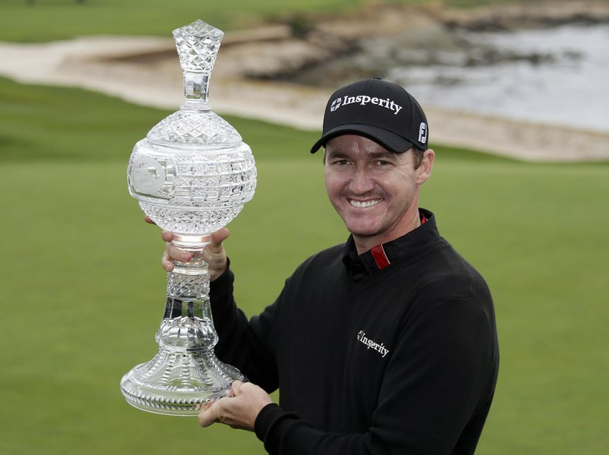 Jimmy Walker poses with his trophy on the 18th green of the Pebble Beach Golf Links after winning the AT&T Pebble Beach Pro-Am golf tournament Sunday, Feb. 9, 2014, in Pebble Beach, Calif. Walker shot a 2-over-par 74 to finish at total 11-under-par. (AP Photo/Eric Risberg)