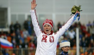 Russia's Olga Graf celebrates raises her hands to acknowledge the crowd during the flower ceremony after winning bronze in the women's 3,000-meter speedskating race at the Adler Arena Skating Center during the 2014 Winter Olympics, Sunday, Feb. 9, 2014, in Sochi, Russia. (AP Photo/Pavel Golovkin)
