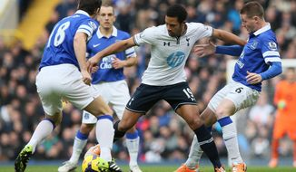 Tottenham's Mousa Dembele, centre defends the ball from Everton's James McCarthy during their English Premier League soccer match between Tottenham Hotspur and Everton at the White Hart Lane stadium in London, Sunday, Feb. 9,  2014. (AP Photo/Alastair Grant)
