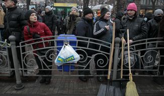Demonstrators angered by more than two months of anti-government protests in Kiev gather on  Khreschatyk street in  Kiev, Ukraine,  Saturday, Feb. 8, 2014. Thousands of people angered by months of anti-government protests in the Ukrainian capital converged on one of the protesters' barricades Saturday, but retreated after meeting sizeable resistance. (AP Photo/Sergei Chuzavkov)
