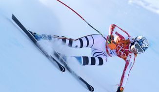 Germany's Maria Hoefl-Riesch makes a turn in a women's downhill training run for the Sochi 2014 Winter Olympics, Friday, Feb. 7, 2014, in Krasnaya Polyana, Russia. (AP Photo/Alessandro Trovati)