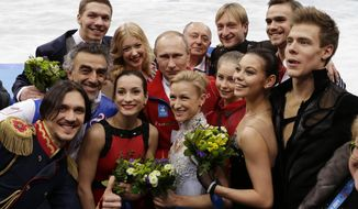 Russian President Vladimir Putin, centre back, poses for a photograph with the Russian team after they placed first in the team figure skating competition at the Iceberg Skating Palace during the 2014 Winter Olympics, Sunday, Feb. 9, 2014, in Sochi, Russia. (AP Photo/David J. Phillip )
