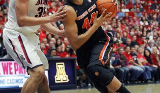 Oregon State's Devon Collier (44) drives the lane against Arizona's Kaleb Tarczewski (35) in the first half of an NCAA college basketball game on Sunday, Feb. 9, 2014, in Tucson, Ariz. (AP Photo/John MIller)