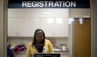 A worker is seen behind the registration window of the emergency room at Grady Memorial Hospital in Atlanta on Jan. 24, 2014. (Associated Press) **FILE**