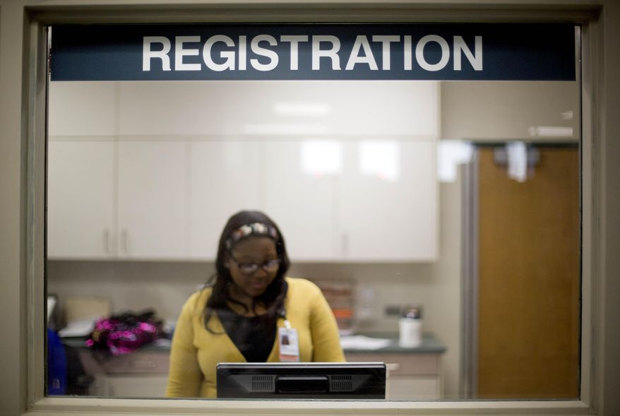 A worker is seen behind the registration window of the emergency room at Grady Memorial Hospital in Atlanta on Jan. 24, 2014. (Associated Press) **FILE**