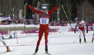 Switzerland's Dario Cologna crosses the finish line to win the men's cross-country 30k skiathlon at the 2014 Winter Olympics, Sunday, Feb. 9, 2014, in Krasnaya Polyana, Russia. (AP Photo/Gregorio Borgia)