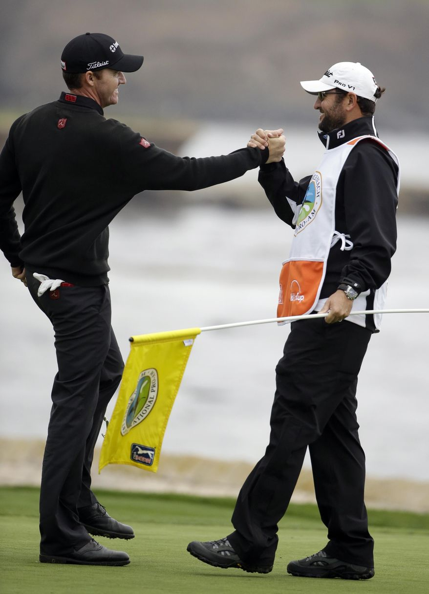 Jimmy Walker, left, celebrates with his caddie Andy Sanders on the 18th green on Sunday, Feb. 9, 2014, after winning the AT&T Pebble Beach Pro-Am golf tournament in Pebble Beach, Calif. (AP Photo/Eric Risberg)