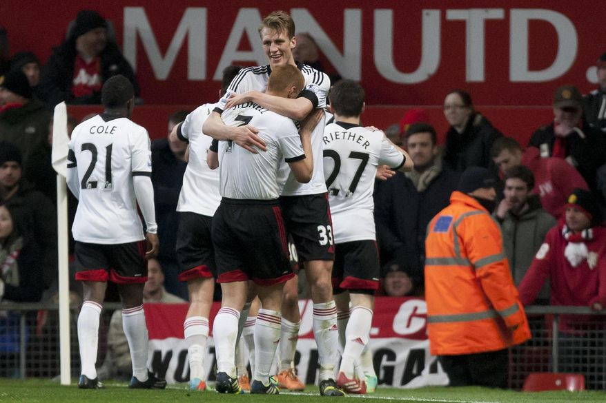 Fulham players celebrate after they drew 2-2 with a late goal from Darren Bent during their English Premier League soccer match against Manchester United at Old Trafford Stadium, Manchester, England, Sunday Feb. 9, 2014. (AP Photo/Jon Super)