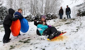 Sledding teammates Ruby Catterson, front, and Maya Hanson, both 9, sail down the hill at Madison Elementary School in Olympia, Wa., Sunday, Feb. 9, 2014 as a vigorous February snowstorm blanketed the region overnight. Many areas were surprised,reporting over 4 inches of snow as warmer temperatures and wetter weather pattern approaches for the week.  (AP Photo/The Olympian, Steve Bloom)