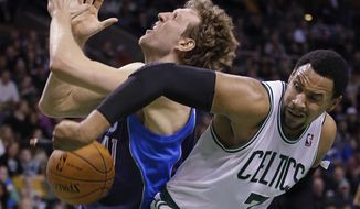 Boston Celtics center Jared Sullinger (7) knocks the ball away as he fouls Dallas Mavericks power forward Dirk Nowitzki (41) going to the hoop during the second half of their NBA basketball game in Boston, Sunday, Feb. 9, 2014. The Mavericks defeated the Celtics 102-91. (AP Photo/Stephan Savoia)