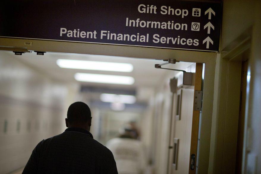 ** FILE ** In this Friday, Jan. 24, 2014, photo, a sign points visitors toward the financial services department at Grady Memorial Hospital, in Atlanta. (AP Photo/David Goldman)