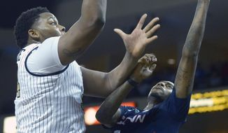 Central Florida center Justin McBride, left, puts up a shot in front of Connecticut forward Phillip Nolan (0) during the second half of an NCAA college basketball game in Orlando, Fla., Sunday, Feb. 9, 2014. Connecticut won 75-55. (AP Photo/Phelan M. Ebenhack)