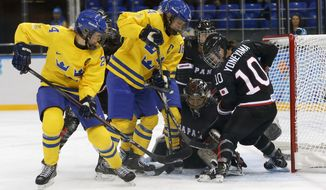 Erika Grahm and Jenni Asserholt of Sweden battle Goalkeeper Nana Fujimoto and Haruna Yoneyama of Japan, (L-R) in front of the net during the 2014 Winter Olympics women's ice hockey game at Shayba Arena, Sunday, Feb. 9, 2014, in Sochi, Russia. (AP Photo/Petr David Josek)
