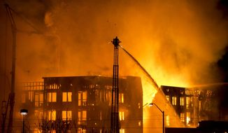Firefighters battle an apartment fire in Salt Lake City, Sunday, Feb. 9, 2014. The apartment building that was under construction. Agency spokesman Jasen Asay told The Associated Press that the Fire Department did a walkthrough of the building on Saturday. (AP Photo/The Salt Lake Tribune, Lennie Mahler)