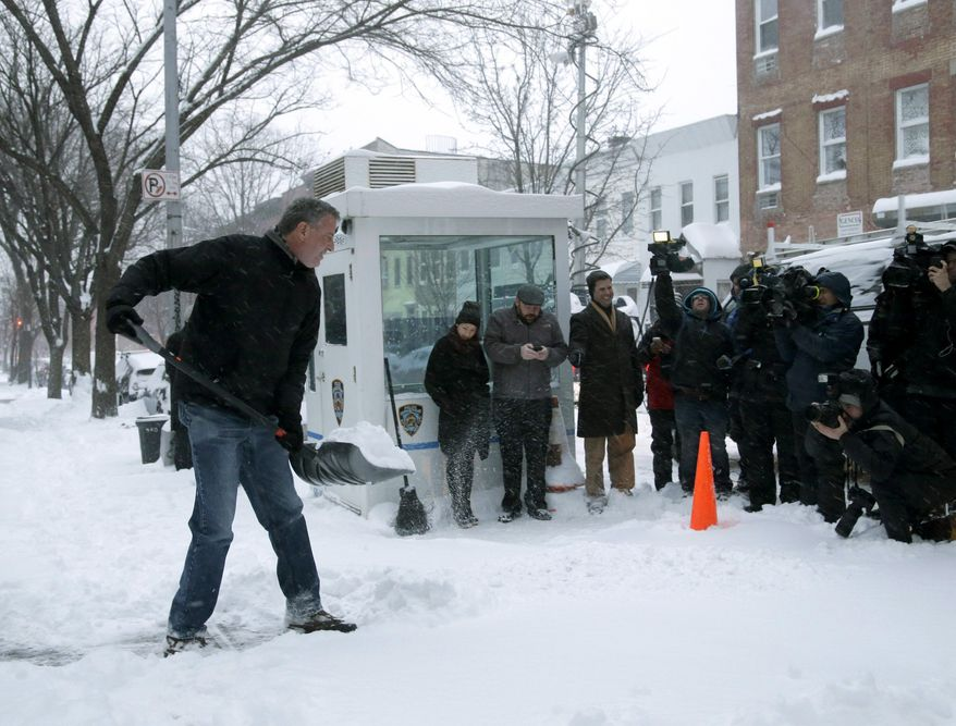 FILE- In this Jan. 3, 2014 file photo, New York City Mayor Bill de Blasio shovels the sidewalk in front of his New York City home in front of the media gathered to record the event. Experts say de Blasio, a former political operative, is using carefully chosen events and images to cultivate the appearance of being an average New Yorker focused on fixing the city's widening income inequality. (AP Photo/Seth Wenig, File)