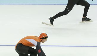Stefan Groothuis of the Netherlands falls as he takes the start with Mitchell Whitmore of the U.S., top, for the second heat of the men's 500-meter speedskating race at the Adler Arena Skating Center during the 2014 Winter Olympics, Monday, Feb. 10, 2014, in Sochi, Russia. (AP Photo/Patrick Semansky)