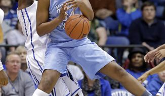North Carolina's Xylina McDaniel and Duke's Elizabeth Williams, left, struggle for possession of a rebound during the first half of an NCAA college basketball game in Durham, N.C., Monday, Feb. 10, 2014. (AP Photo/Gerry Broome)