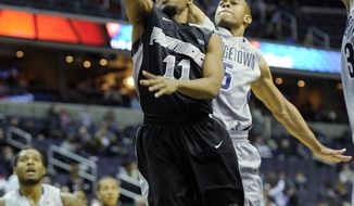 Providence guard Bryce Cotton (11) goes to the basket against Georgetown guard Markel Starks (5) during the first half of an NCAA college basketball game, Monday, Feb. 10, 2014, in Washington. (AP Photo/Nick Wass)