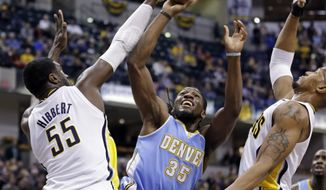 Denver Nuggets forward Kenneth Faried (35) shoots between Indiana Pacers center Roy Hibbert (55) and David West in the first half of an NBA basketball game in Indianapolis, Monday, Feb. 10, 2014. (AP Photo/Michael Conroy)