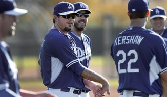 Los Angeles Dodgers pitcher Josh Beckett, center, stretches during spring training baseball practice Monday, Feb. 10, 2014, in Glendale, Ariz. (AP Photo/Paul Sancya)