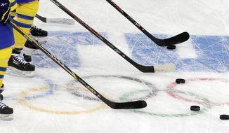 Members of Sweden's women's ice hockey team run warm up drills before facing Japan during the 2014 Winter Olympics women's ice hockey game at Shayba Arena, Sunday, Feb. 9, 2014, in Sochi, Russia. (AP Photo/Matt Slocum)