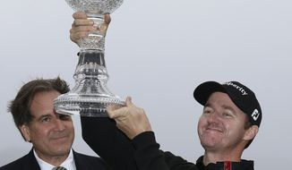 Jimmy Walker lifts his trophy on the 18th green of the Pebble Beach Golf Links after winning the AT&T Pebble Beach Pro-Am golf tournament Sunday, Feb. 9, 2014, in Pebble Beach, Calif. Walker shot a 2-over-par 74 to finish at total 11-under-par. At left is broadcaster Jim Nantz. (AP Photo/Eric Risberg)