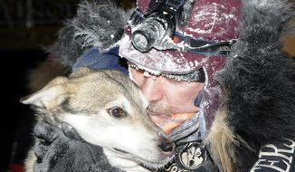 Two Rivers musher Allen Moore kisses his lead dog, Quito, after winning his second consecutive Yukon Quest International Dog Sled Race in Whitehorse, Yukon, Monday, Feb. 10, 2014. (AP Photo/The Canadian Press/Whitehorse Star, Marcel Vander Wier)