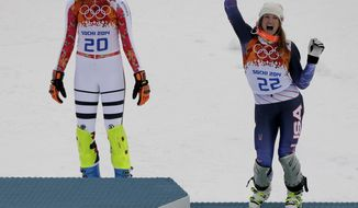 Women's supercombined bronze medalist United States' Julia Mancuso, right,  celebrates while Germany's gold medalist Maria Hoefl-Riesch, left, waits to take the podium during a flower ceremony at the Alpine ski venue at the Sochi 2014 Winter Olympics, Monday, Feb. 10, 2014, in Krasnaya Polyana, Russia. (AP Photo/Charlie Riedel)