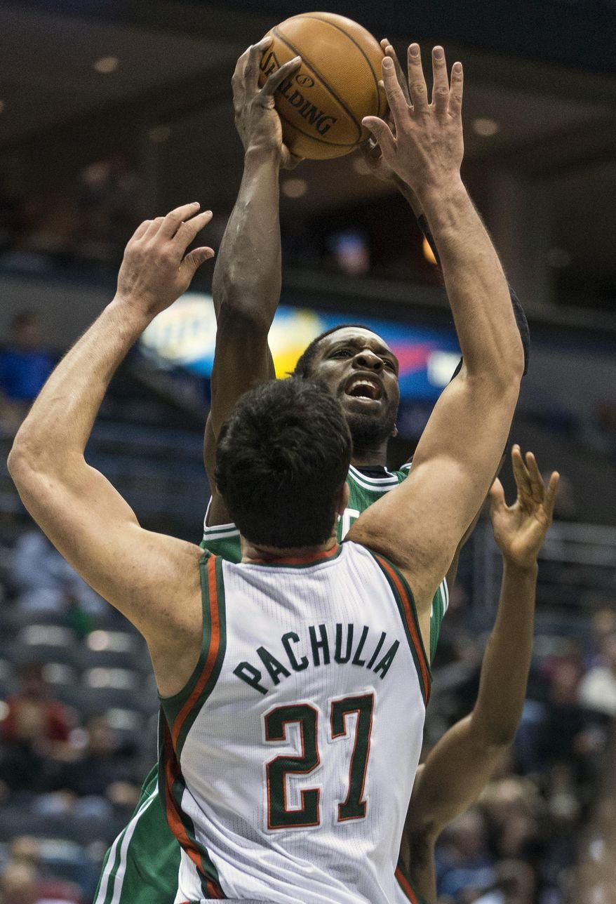 Milwaukee Bucks' Zaza Pachulia tries to block Boston Celtics' Jeff Green during the first half of an NBA basketball game, Monday, Feb. 10, 2014, in Milwaukee. (AP Photo/Tom Lynn)