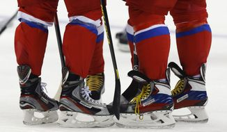 Russia forward Alexander Radulov, left, forward Ilya Kovalchuk, center and forward Alexander Ovechkin huddle during a training session at the 2014 Winter Olympics, Monday, Feb. 10, 2014, in Sochi, Russia. (AP Photo/Julie Jacobson)