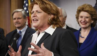 FILE - In this Feb. 4, 2014 file photo, Senate Agriculture Committee member Sen. Heidi Heitkamp, D-N.D., center, joined by fellow committee members, gestures during a news conference on Capitol Hill in Washington after congressional approval of a sweeping five-year farm bill that provides food for the needy and subsidies for farmers. Looking on are Sen. John Hoeven, R-N.D., left, and committee chair Sen. Debbie Stabenow, D-Mich.  Heitkamp spent this past weekend in Cuba, where she talked with officials about farm exports from North Dakota and the state's trade relationship with the island nation. (AP Photo/J. Scott Applewhite, File)