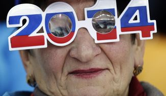 A skating fan wears glasses in the colors of the Russian flag as she watches the men's 500-meter speedskating race at the Adler Arena Skating Center during the 2014 Winter Olympics, Monday, Feb. 10, 2014, in Sochi, Russia. (AP Photo/Matt Dunham)