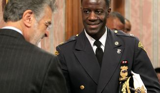 New Cleveland police chief Calvin Williams, right, is congratulated by Mayor Frank Jackson after a ceremony at City Hall, Monday, Feb,10, 2014.  Williams succeeds Michael McGrath, who became the new public safety director.    (AP Photo/The Plain Dealer, Marvin Fong) MANDATORY CREDIT; NO SALES