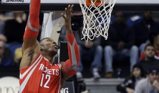 Houston Rockets' Dwight Howard goes for a hook shot as Minnesota Timberwolves' Kevin Love, right, looks on in the first quarter of an NBA basketball game, Monday, Feb. 10, 2014, in Minneapolis. (AP Photo/Jim Mone)