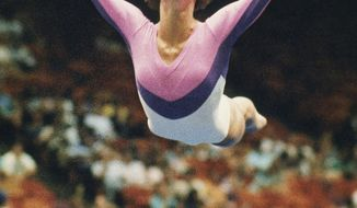 FILE - In this July 1988 file photo, U.S. gymnast Phoebe Mills flies through the air as she performs her floor exercise at the U.S. Gymnastics Championships in Houston, Texas. Mills used to flip for Olympic medals. These days, she decides who wins them. The 1988 U.S. gymnastics champion and Olympic bronze medalist is working in the snowboarding judging booth at the Sochi Games, giving marks in both the halfpipe and slopestyle contests at Rosa Khutor Extreme Park.  (AP Photo/David Breslauer, File)